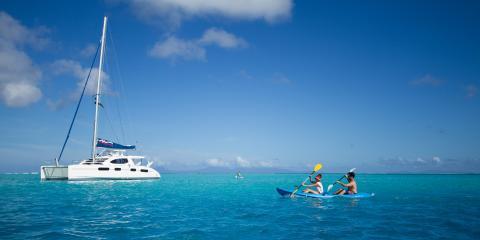 Sailing catamaran in Tahiti with kayakers